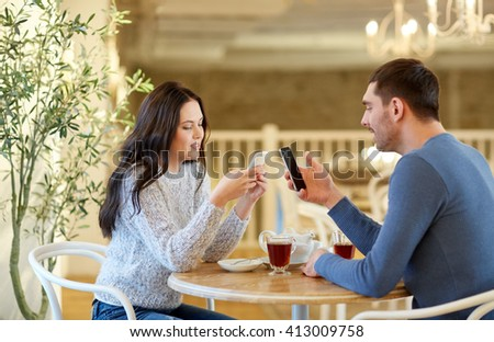 people, communication and dating concept - happy couple with smartphones drinking tea at cafe or restaurant