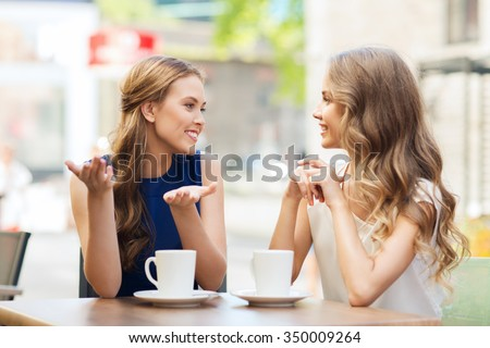 people, communication and friendship concept - smiling young women drinking coffee or tea and talking at outdoor cafe - stock photo