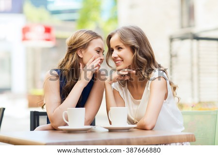 people, communication and friendship concept - smiling young women drinking coffee or tea and gossiping at outdoor cafe - stock photo