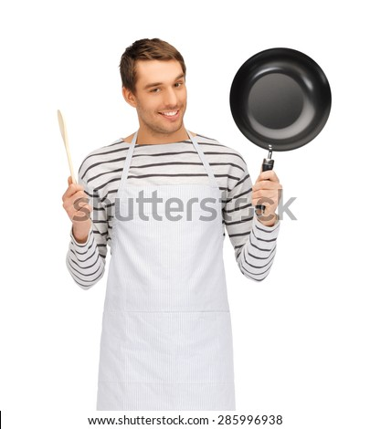 people, cooking and culinary concept - happy man or cook in apron with frying pan and wooden spoon - stock photo