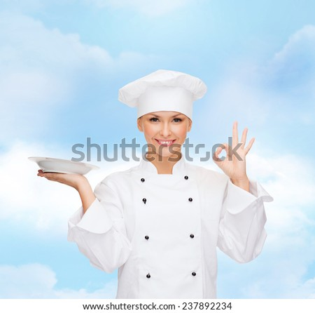 people, cooking and food concept - smiling female chef, cook or baker with empty plate showing ok sign over blue cloudy sky background - stock photo