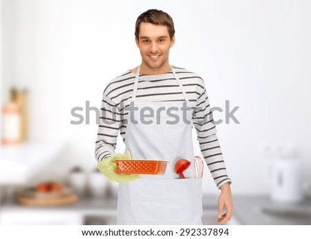 people, cooking, culinary and food concept - happy man or cook in apron with baking and kitchenware over home kitchen background - stock photo
