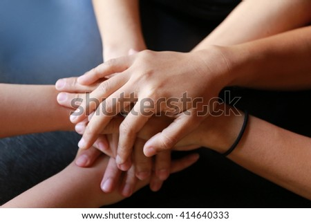 people, cooperation and team work concept - close up of creative team sitting at table and holding hands on top of each,  teamwork hand group