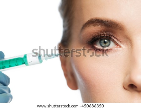 people, cosmetology, plastic surgery and beauty concept - beautiful young woman face and beautician hand in glove with syringe making injection over white background - stock photo