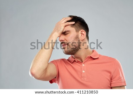 people, crisis, emotions and stress concept - unhappy man suffering from head ache over gray background - stock photo