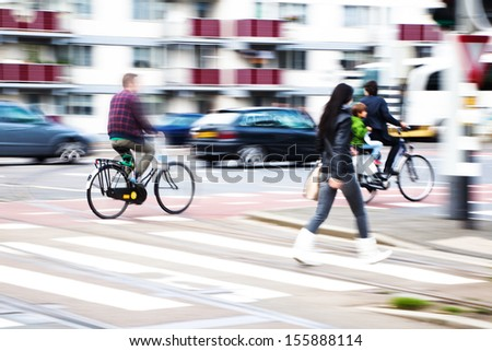 people crossing a busy city street in motion blur  - stock photo