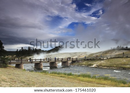 People crossing bridge over the Firehole River in the Midway Geyser Basin of Yellowstone National Park. - stock photo