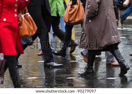 people crossing the street on a rainy day - stock photo