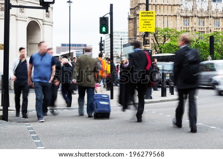 people crowd in motion blur crossing a street near Big Ben in London - stock photo