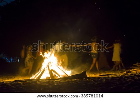 People dancing around the fire