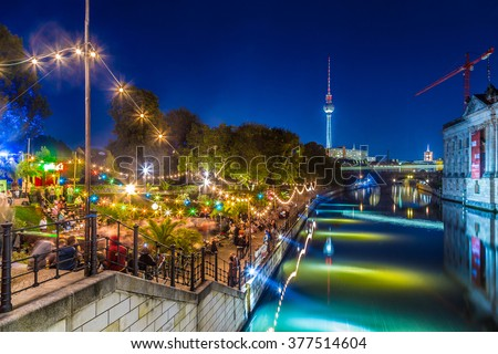People dancing at summer Strandbar beach party near Spree river at historic Museum Island with famous TV tower in the background in twilight during blue hour at dusk, Berlin Mitte district, Germany - stock photo