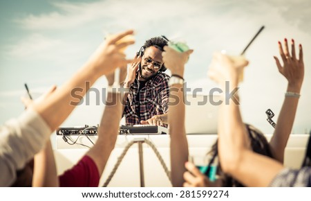 people dancing at the concert with hands up. famous dj set on the move. concept about party, music and people - stock photo