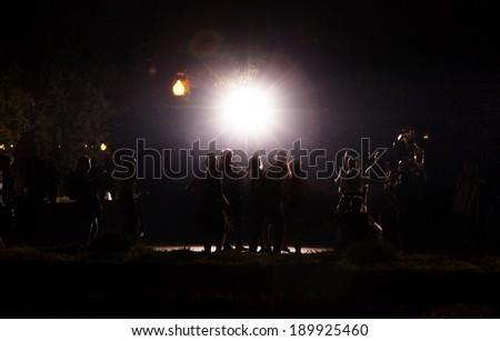 People dancing below spotlight - stock photo
