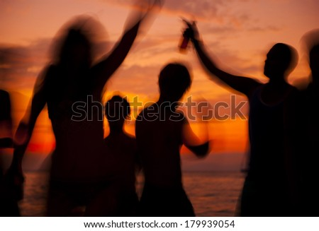 People Dancing on The Beach at Sunset - stock photo