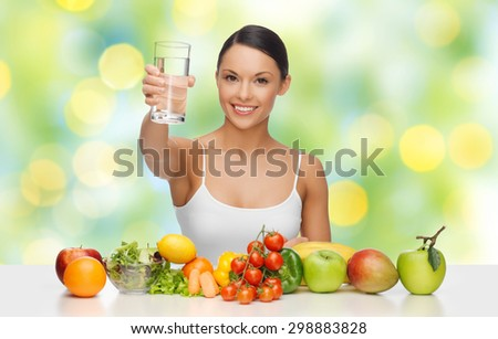 people, diet and vegetarian concept - happy asian woman with healthy food showing glass of water over green lights background - stock photo