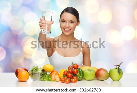 people, diet and vegetarian concept - happy asian woman with healthy food showing glass of water over blue lights background - stock photo