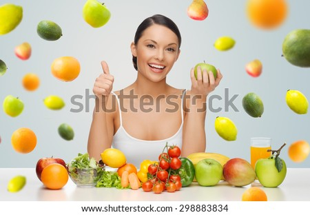 people, diet, gesture and vegetarian concept- happy asian woman with healthy food showing thumbs up over gray background with falling fruits - stock photo