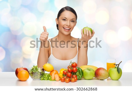 people, diet, gesture and vegetarian concept- happy asian woman with healthy food showing thumbs up over blue lights background - stock photo
