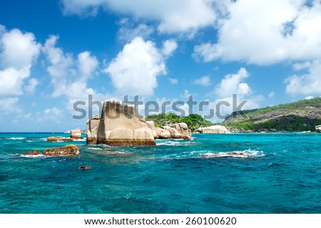 People do Snorkelling near rocky reefs. The Seychelles. - stock photo