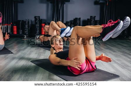 People doing abs in a fitness class - stock photo