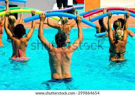 people doing water aerobics in a pool of a resort - stock photo