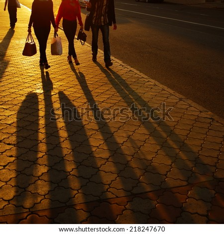 people down the street in sun sunshine - stock photo