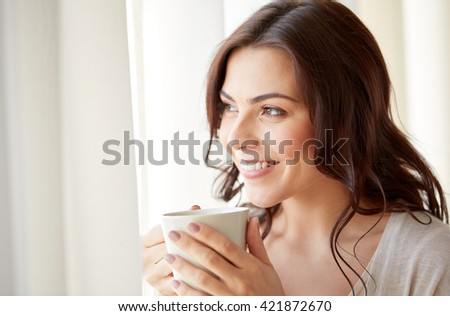 people, drinks and leisure concept - happy young woman with cup of tea or coffee at home