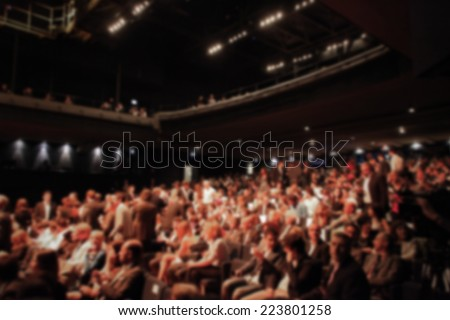People during a show. Intentionally blurred background.