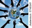 People & Earth: A circle of human hands reach out to the Earth in the Sky. - stock photo