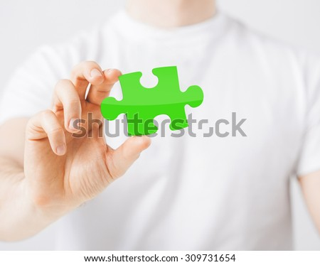 people, ecology and green energy concept - close up of man holding green puzzle piece