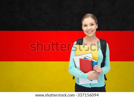 people, education, learning and school concept - happy and smiling teenage student girl with books and backpack over german flag background - stock photo