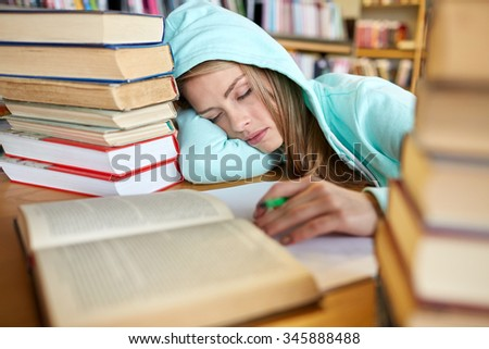 people, education, session, exams and school concept - tired student girl or young woman with books sleeping in library - stock photo