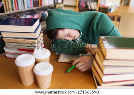 people, education, session, exams and school concept - tired student or young man with books and coffee sleeping in library - stock photo