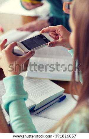 people, education, technology and exam concept - close up of student hands with smartphone taking picture of books page and making cheat sheet in school library