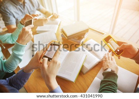 people, education, technology and exam concept - close up of students with smartphones taking picture of books page and making cheat sheet in school library - stock photo