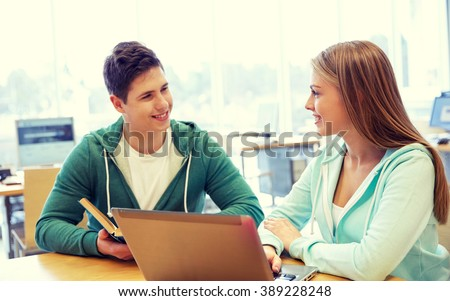 people, education, technology and school concept - happy students with laptop computer and books in library - stock photo
