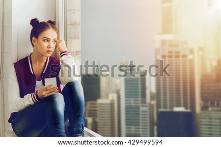 people, emotion, technology and teens concept - sad unhappy pretty teenage girl sitting on windowsill with smartphone and looking to window - stock photo