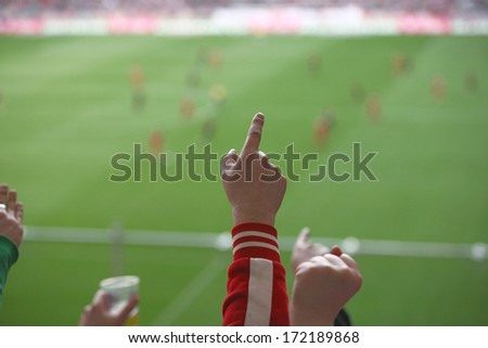 people encouraging their team in a soccer stadion, focus is on the hands - stock photo
