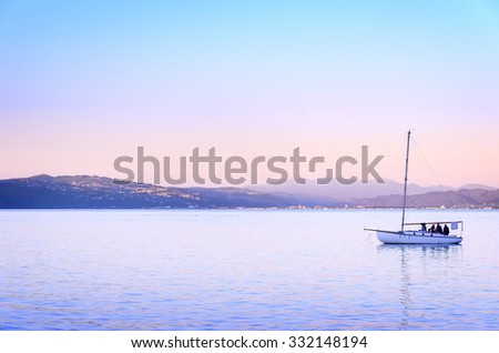 People enjoy the sunset on a sailboat in the ocean harbor in Wellington, New zealand - stock photo
