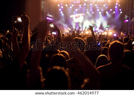 People enjoying a concert holding their hands up and recording with their smart phones.