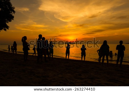 People enjoying sunset on the beach at koh chang island, Thailand