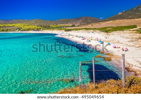 People enjoying the sunny weather on sandy Grand Capo beach with red rocks near Ajaccio, Corsica, Europe.