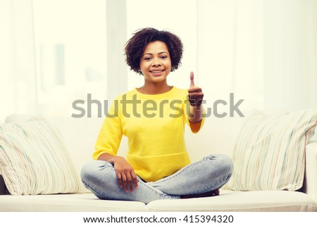 people, ethnicity, gesture and leisure concept - happy african american young woman showing thumbs up and sitting on sofa at home - stock photo