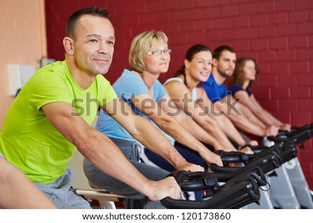 People exercising in a spinning course in fitness center - stock photo
