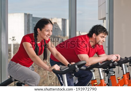 People exercising on bicycles in fitness gym. Couple exercising by spinning on stationary bicycles. - stock photo
