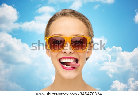people, expression, joy and fashion concept - smiling young woman in sunglasses with pink lipstick on lips showing tongue over blue sky and clouds background - stock photo