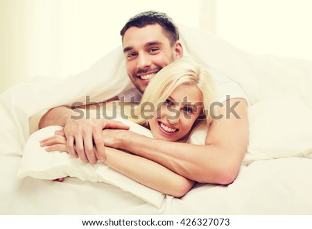 people, family, bedtime and happiness concept - happy couple lying in bed and hugging at home