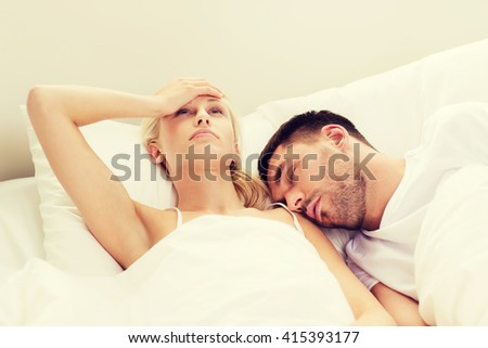 people, family, bedtime and insomnia concept - unhappy woman having sleepless night with sleeping and snoring man in bed at home