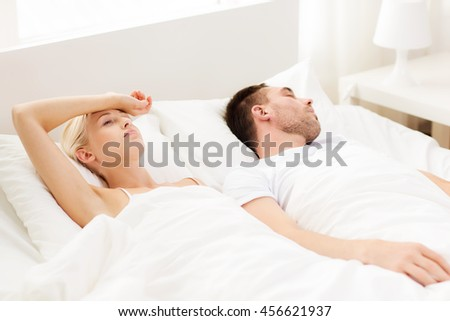 people, family, bedtime and insomnia concept - unhappy woman having sleepless night with sleeping man in bed at home