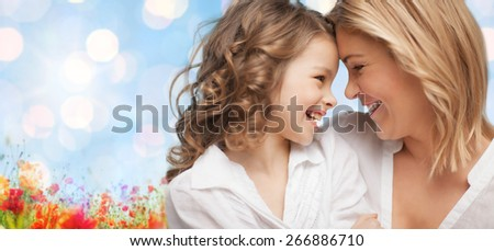 people, family, love and harmony concept - happy mother and daughter cuddling over blue sky and poppy field n background - stock photo